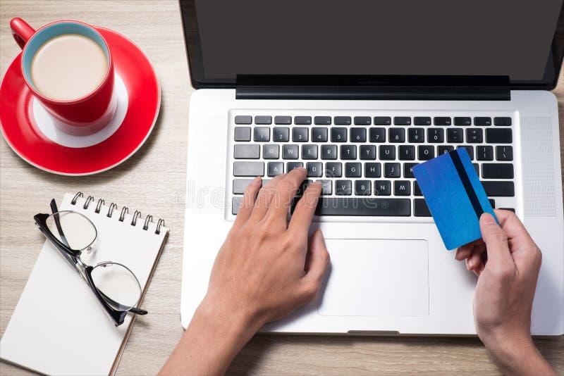 Hållande kreditkort för man On-line shopping på använda för internet royaltyfria foton