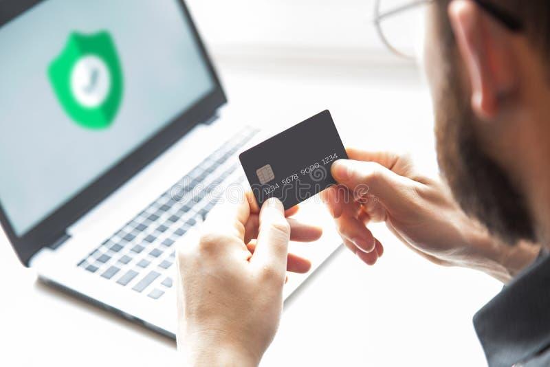 Hållande kreditkort för man och använda bärbar datordatoren On-line shoppingbegrepp royaltyfria foton