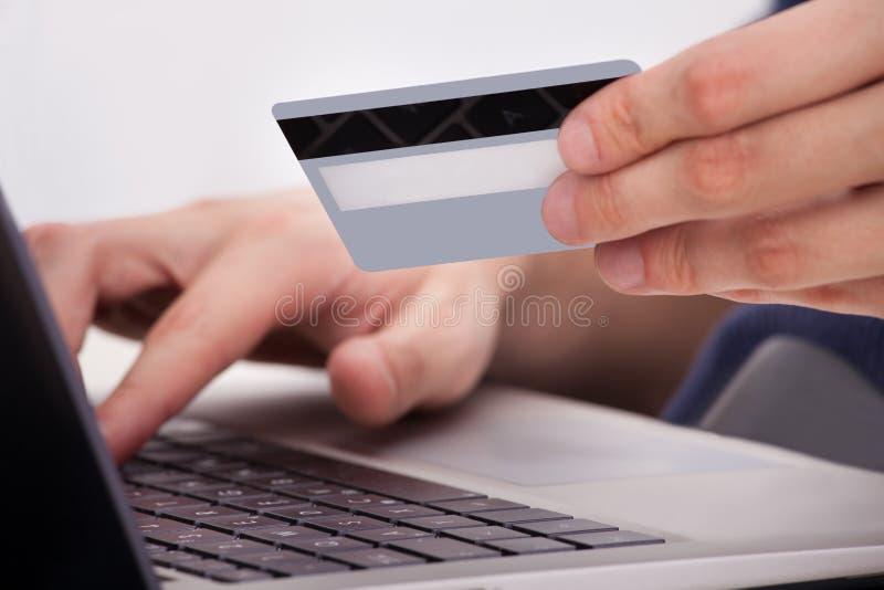 Hållande kreditkort för person genom att använda bärbara datorn fotografering för bildbyråer