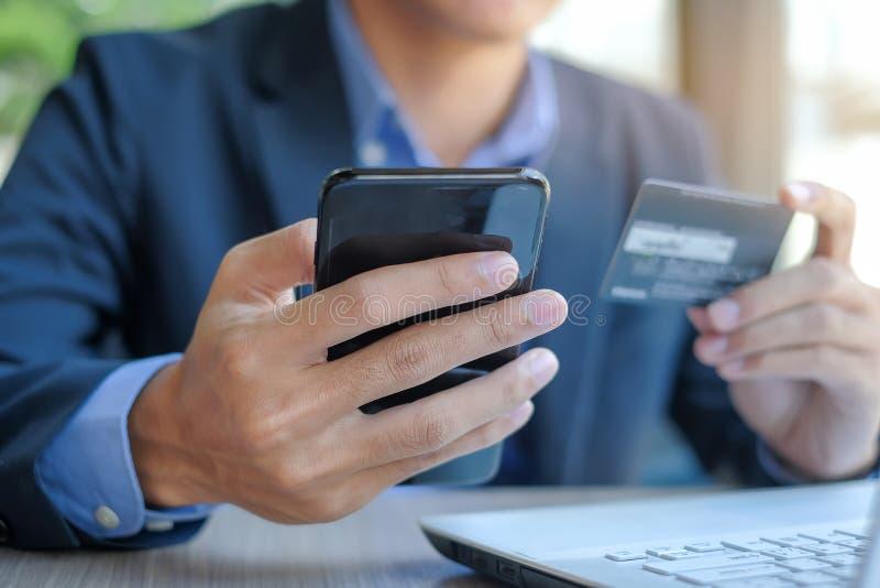Hållande kreditkort- och användasmartphone för online-shopping, medan göra beställningar royaltyfri fotografi
