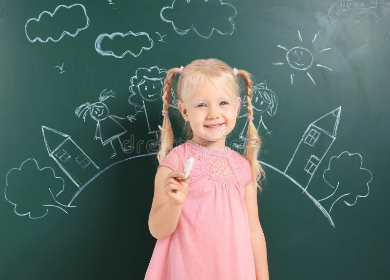 Hållande krita för litet barn nära svart tavla med teckningen royaltyfria foton