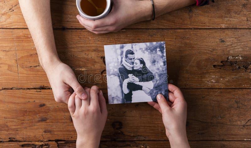 Hållande kvinnas för oigenkännlig man hand Se deras foto Par royaltyfri bild