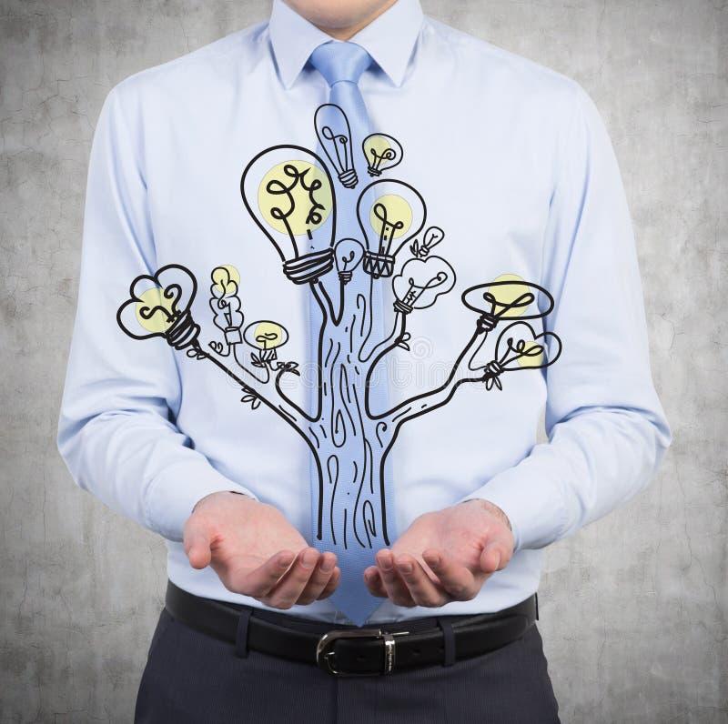 Hållande lampträd för affärsman arkivfoto