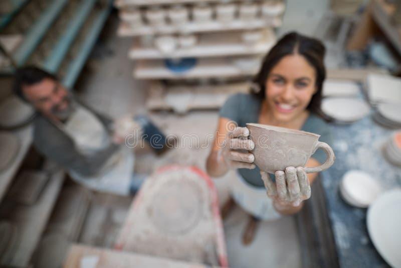 Hållande lerakopp för kvinnlig keramiker arkivfoto