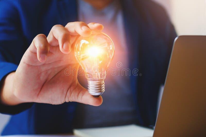 hållande lightbulb för affärsman i regeringsställning idérik idé för savin royaltyfria foton
