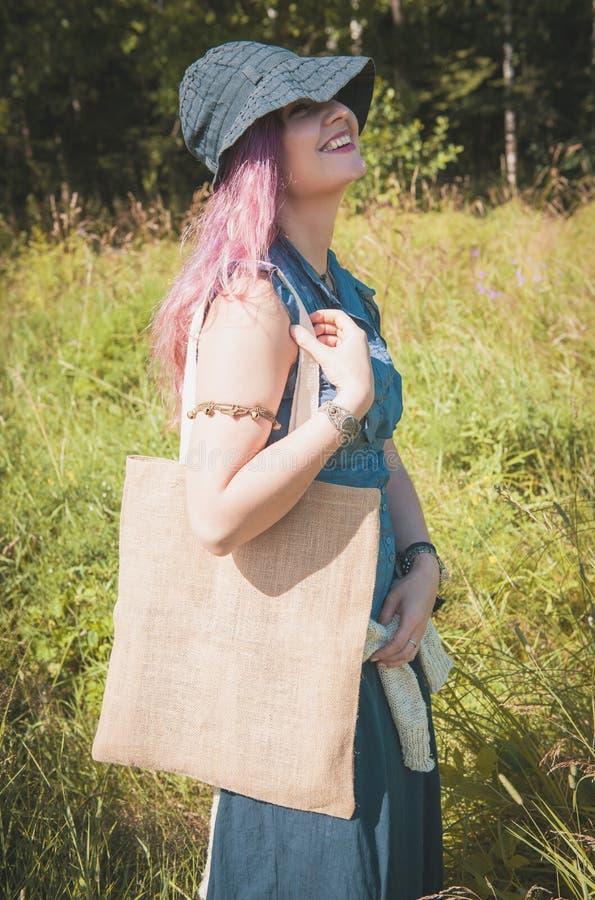 Hållande linnepåse för lycklig kvinna i sommarfält Mallåtlöje upp arkivbild