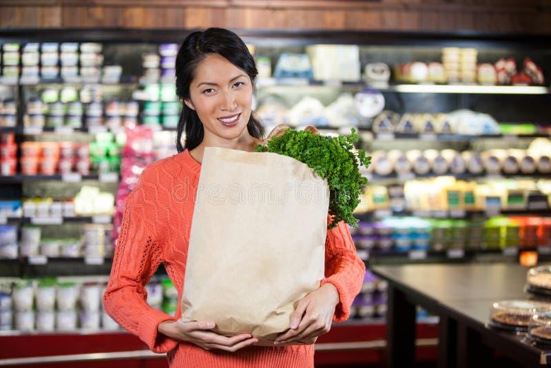Hållande livsmedel för kvinna i pappers- påse arkivfoto