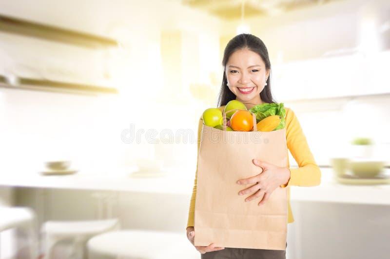Hållande livsmedelpåse för kvinna i kök royaltyfria bilder