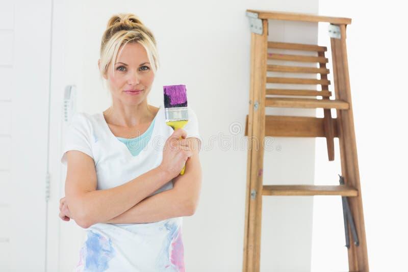 Hållande målarfärgborste för härlig kvinna i nytt hus royaltyfria foton