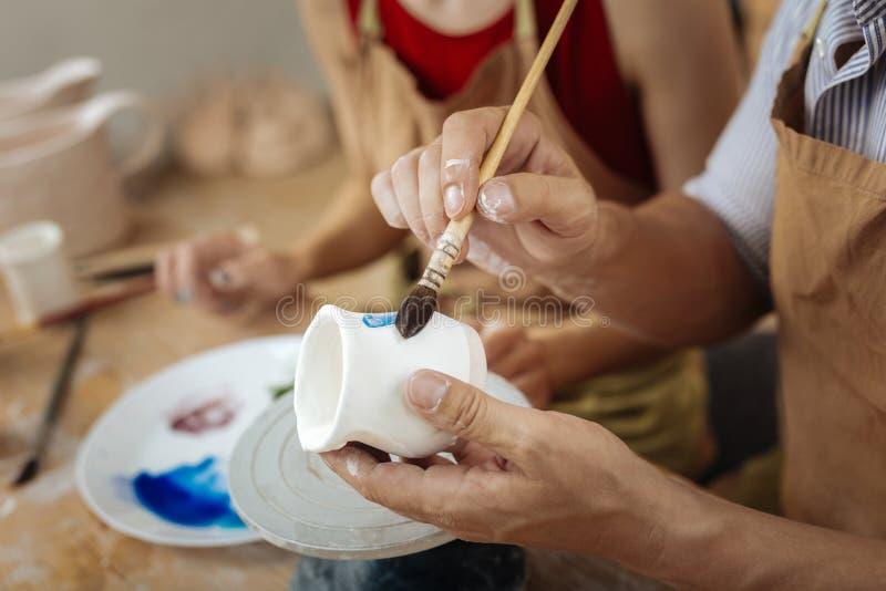 Hållande målningborste för manlig keramiker, medan dekorera lerakrukan fotografering för bildbyråer
