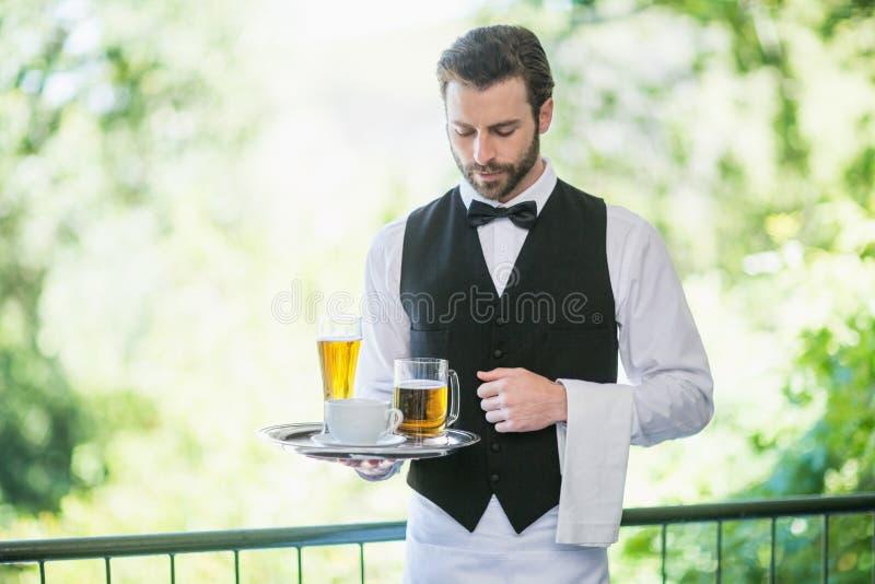 Hållande magasin för manlig uppassare med ölexponeringsglas och kaffekoppen i restaurang royaltyfria foton