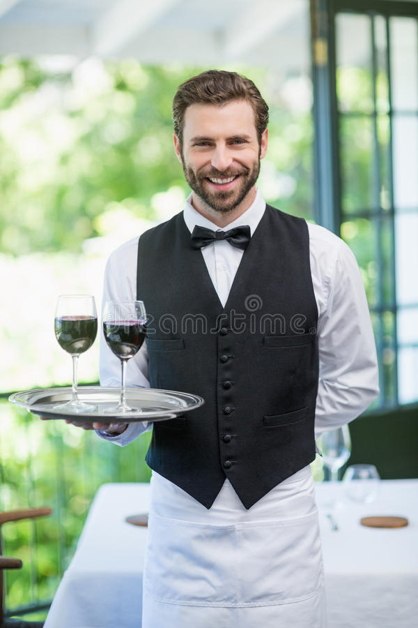 Hållande magasin för manlig uppassare med vinexponeringsglas i restaurangen fotografering för bildbyråer