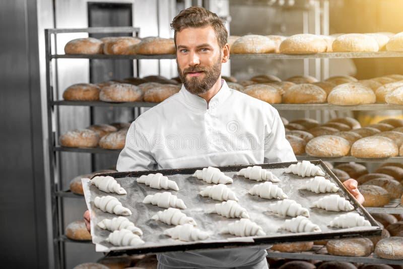 Hållande magasin för stilig bagare som är fullt av nytt bakade croisants arkivbild