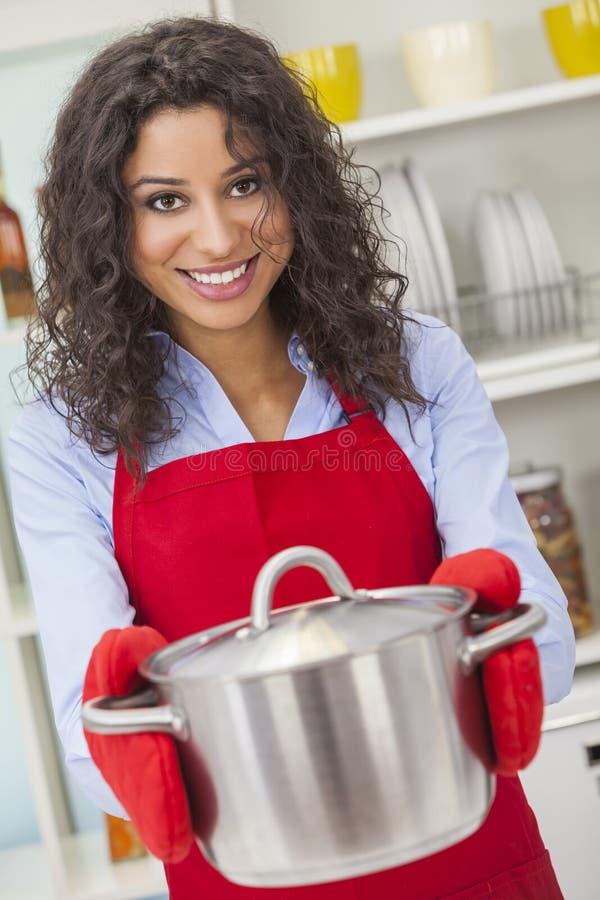 Hållande matlagningkruka för lycklig kvinna i kök arkivbild