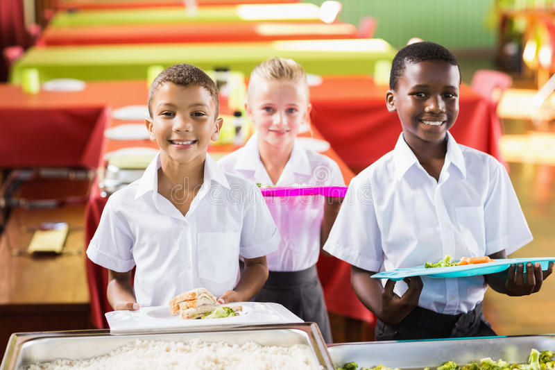 Hållande matmagasin för student i skolakafeteria arkivbilder