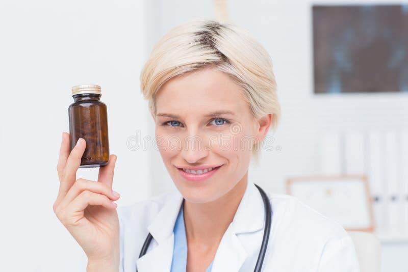 Hållande medicinflaska för säker kvinnlig doktor fotografering för bildbyråer