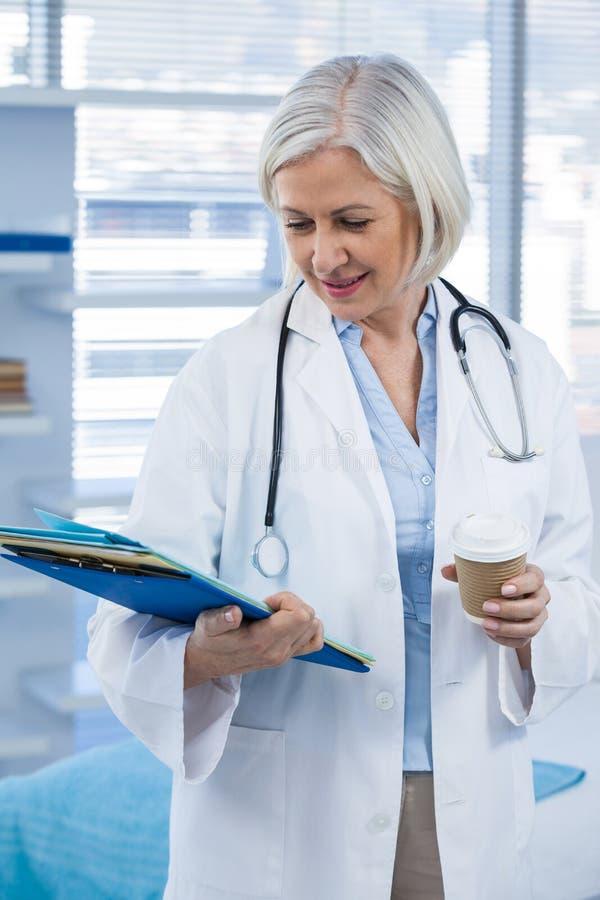 Hållande medicinsk mapp för kvinnlig doktor och kaffekopp royaltyfria bilder