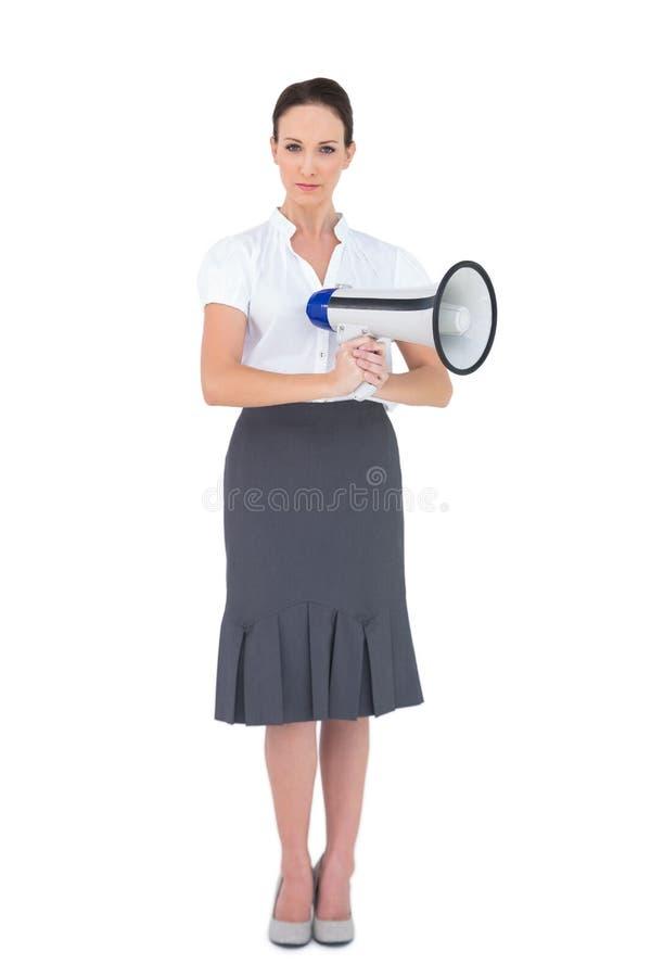 Hållande megafon för Unsmiling affärskvinna arkivbild