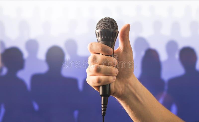 Hållande mikrofon- och visningtummar för hand upp royaltyfri fotografi
