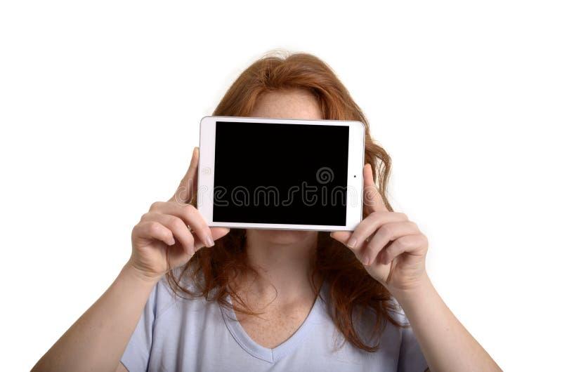 Hållande mini- minnestavlaPC för nätt rödhårig kvinna för framsida royaltyfri bild