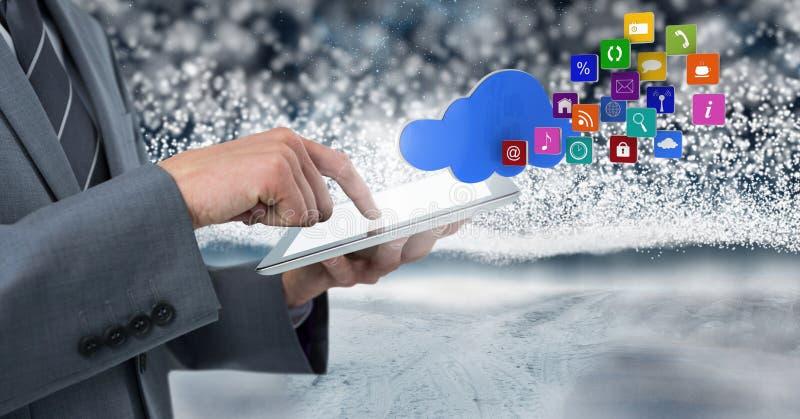 Hållande minnestavla för affärsman med apps och snöbackgorund arkivfoton