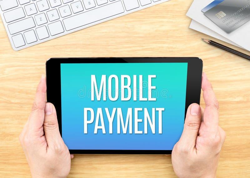 Hållande minnestavla för hand med mobilt betalningord på den wood tabellen, Inte arkivbilder