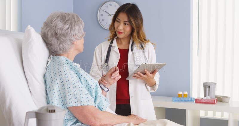 Hållande minnestavladator för japansk doktor som talar till den mogna kvinnan i sjukhussäng fotografering för bildbyråer