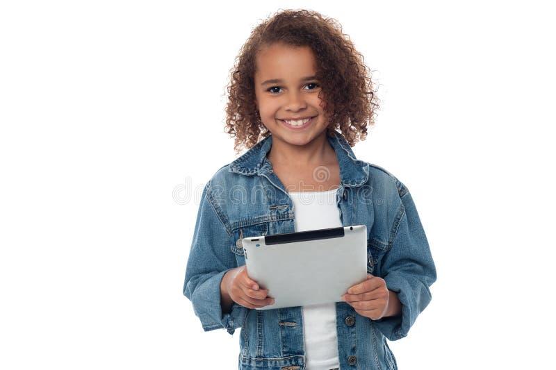 Hållande minnestavlaPC för gullig liten flicka arkivfoton