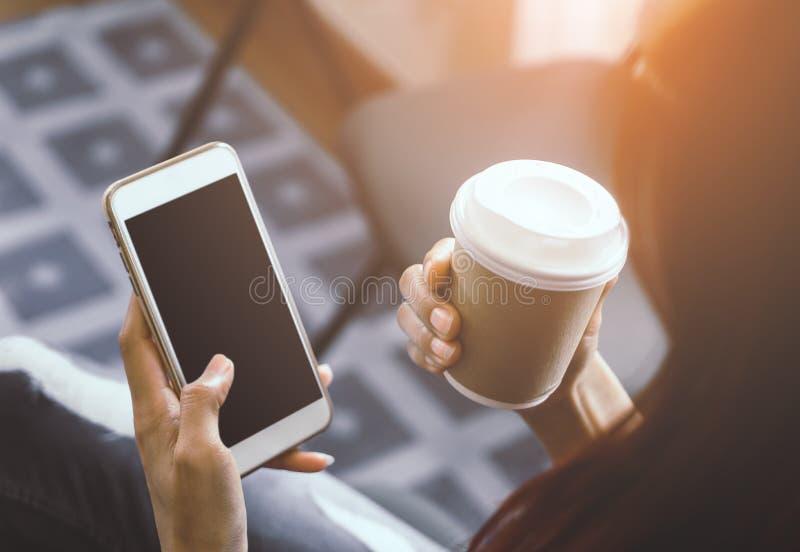 Hållande mobil för tillfällig kvinna med den tomma skärmen och varmt kaffe royaltyfria bilder