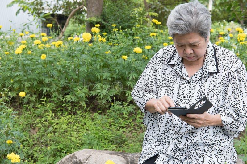 Hållande mobiltelefon för äldre kvinna, medan sitta på bänk i garde royaltyfria bilder