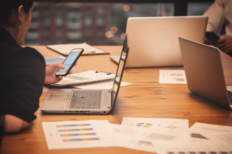 Hållande mobiltelefon för affärsfolk med bärbara datorer arkivfoton