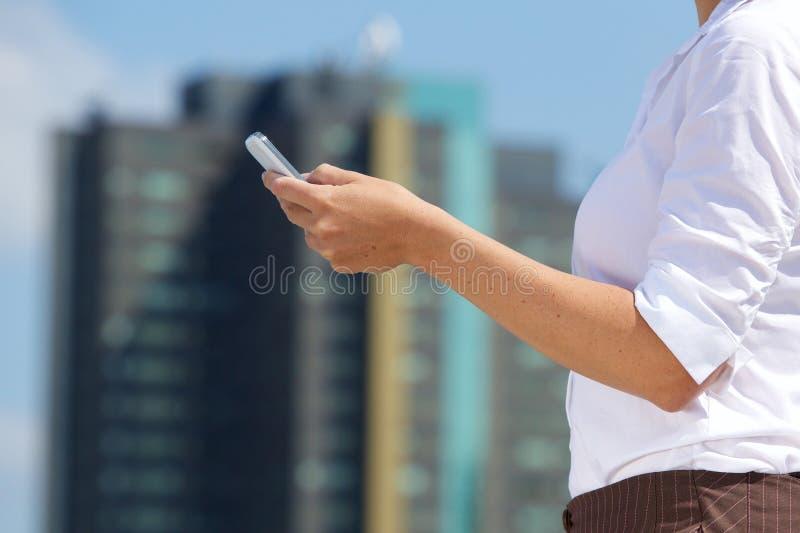 Hållande mobiltelefon för affärskvinna i staden royaltyfri bild