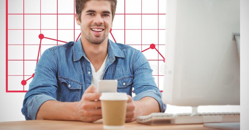 Hållande mobiltelefon för affärsman på skrivbordet mot graf arkivfoton