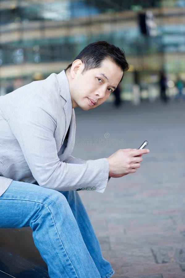 Hållande mobiltelefon för asiatisk man royaltyfria bilder