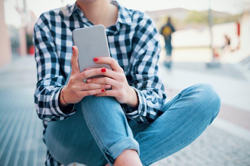 Hållande mobiltelefon för flicka på stadsgatabakgrund royaltyfri bild