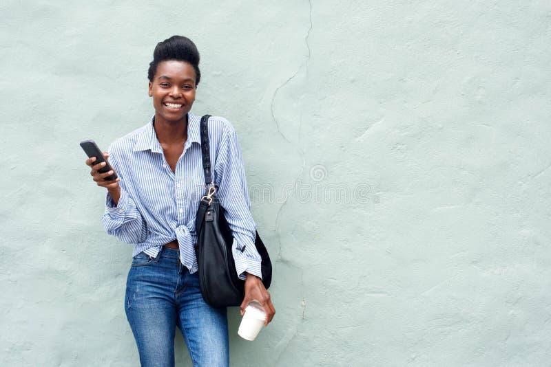 Hållande mobiltelefon för härlig svart kvinna royaltyfri fotografi
