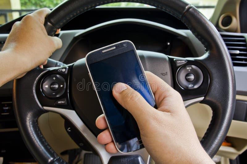 Hållande mobiltelefon för hand i bil royaltyfria bilder