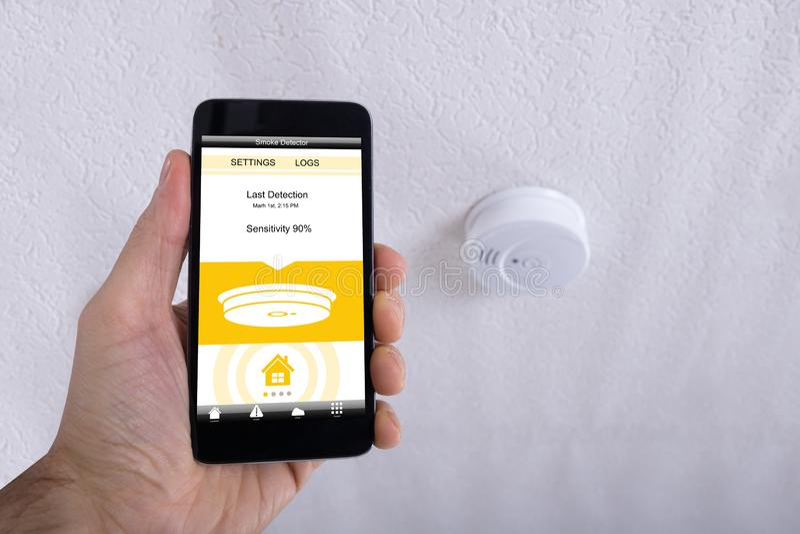Hållande mobiltelefon för hand i Front Of Smoke Detector royaltyfri bild