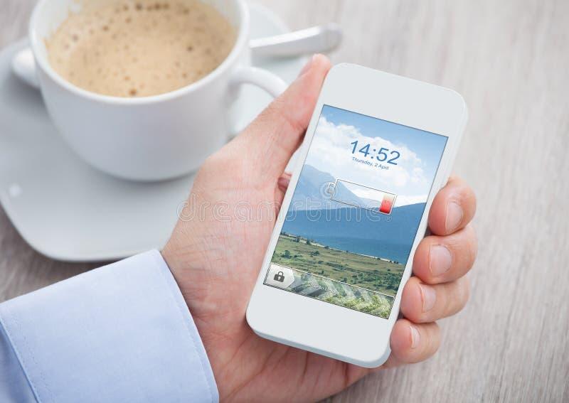 Hållande mobiltelefon för hand med det låga batteriet arkivfoton