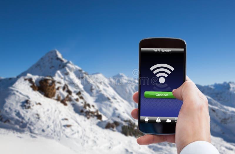 Hållande mobiltelefon för hand med wifisignalen royaltyfri foto