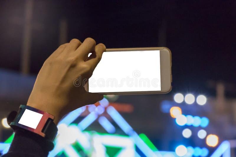 Hållande mobiltelefon för hand till att anteckna i konsert royaltyfri bild
