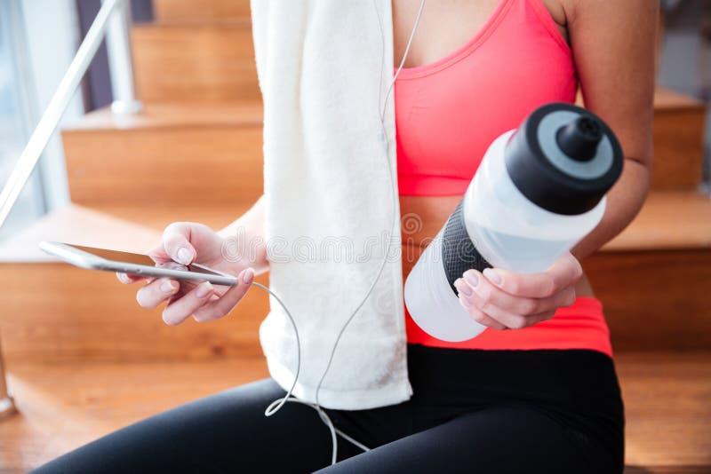 Hållande mobiltelefon för idrottskvinna och flaska av vatten i idrottshall royaltyfria foton