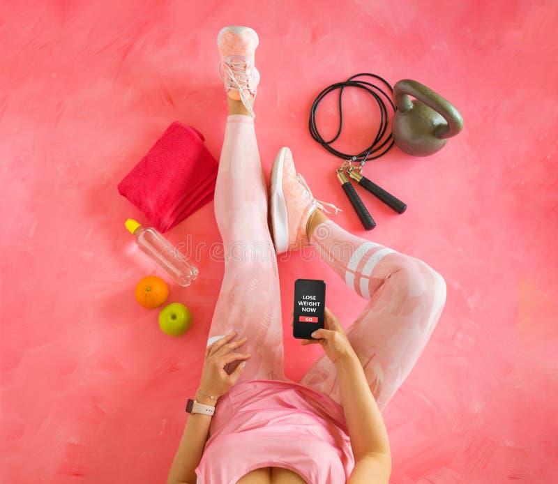 Hållande mobiltelefon för kvinna med kondition app som är klar för utbildning för viktförlust royaltyfria bilder