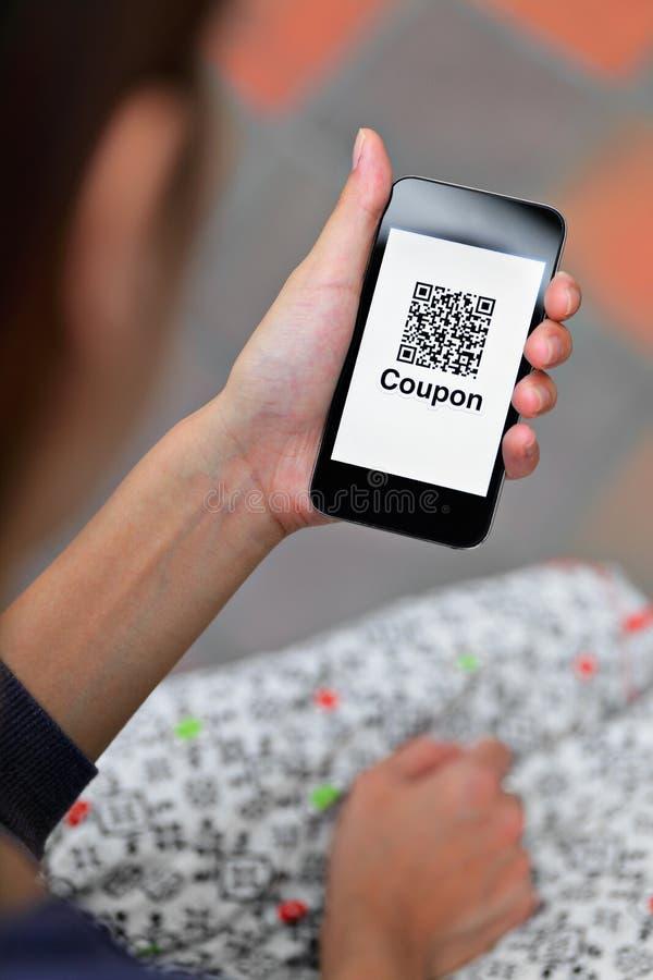 Hållande mobiltelefon för kvinnahand med QR-kodkupongen royaltyfri bild
