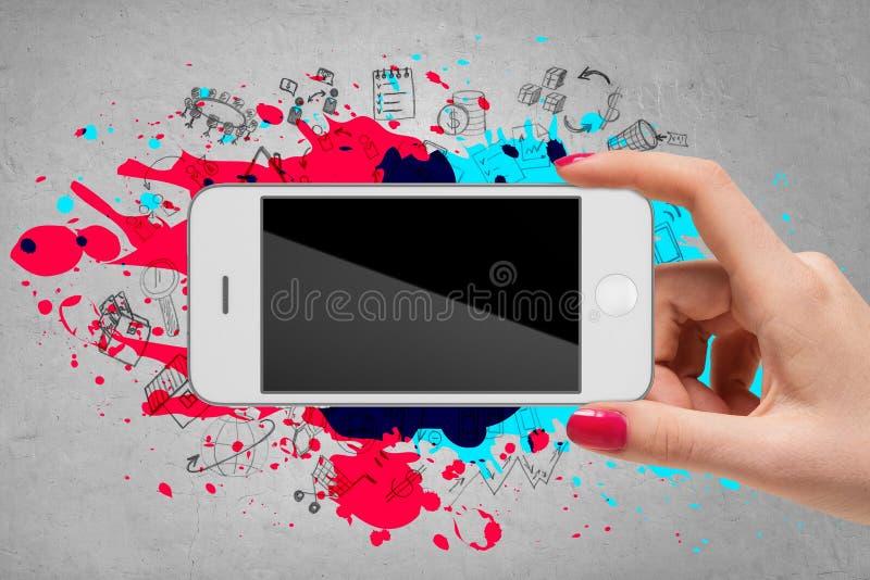 Hållande mobiltelefon för kvinnahand på grå bakgrund royaltyfria foton