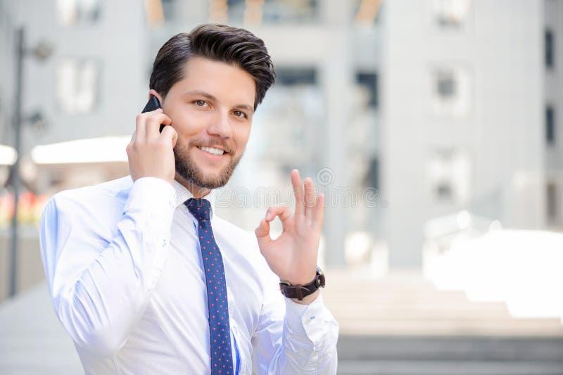 Hållande mobiltelefon för trevlig ung affärsman fotografering för bildbyråer