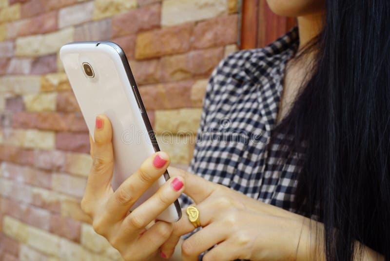 Hållande mobiltelefon för ung flicka, teknologi eller socialt nätverksbegrepp fotografering för bildbyråer
