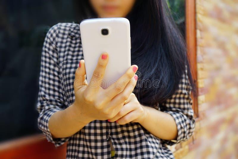 Hållande mobiltelefon för ung flicka, teknologi eller socialt nätverksbegrepp royaltyfria foton
