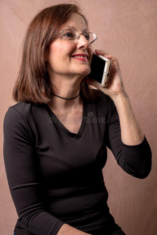 Hållande mobiltelefon för vuxen kvinna royaltyfri foto