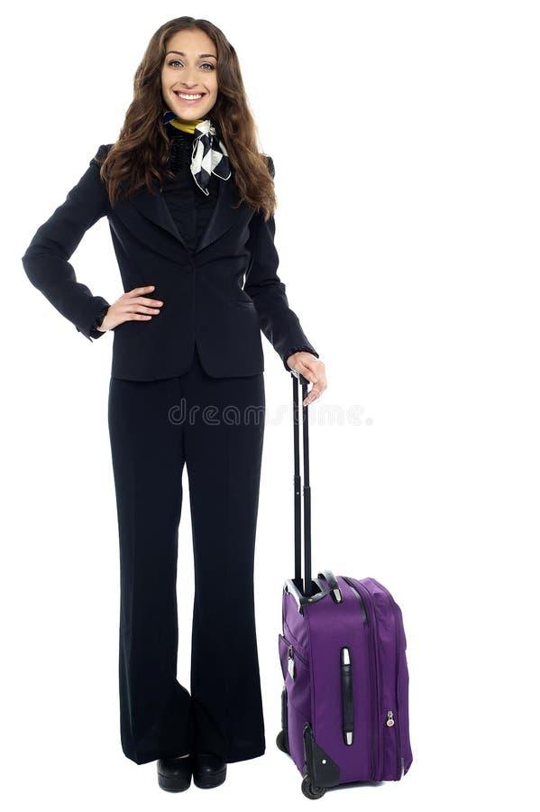 Hållande moderiktig purpurfärgad strolley för gladlynt kvinnahandelsresande royaltyfria foton